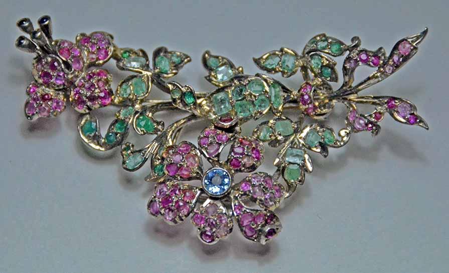 Eccezionale spilla in argento con Rubini, Smeraldi e Topazi blu